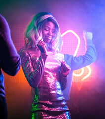 Wall Murals Dance School Happy African girl dancing in night club. Pretty African American woman having fun bright neon glowing. Night life concept. Entertainment concept.