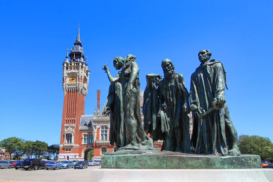 """Calais, France - May 26, 2020 : """"Les Bourgeois de Calais"""", sculpture of Rodin and Calais town hall in the north of France"""
