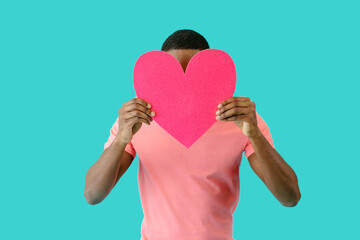 Portrait of a young man holding pink heart in front of head with face obscured, valentine's day love, give your heart concept