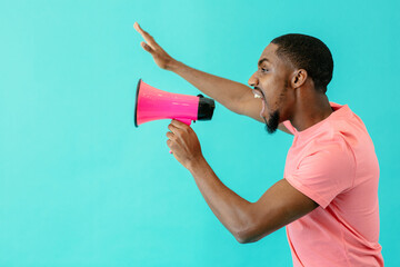 Portrait of a young man shouting through megaphone with  arm up and mouth open