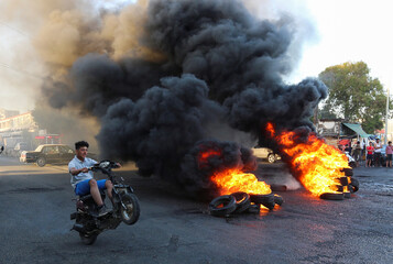 A youth man boy rides his motorbike near burning tires during a sit-in protest against the fall in pound currency and mounting economic hardship, in Ghazieh