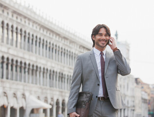 Smiling businessman talking on cell phone in St. Mark's Square in Venice