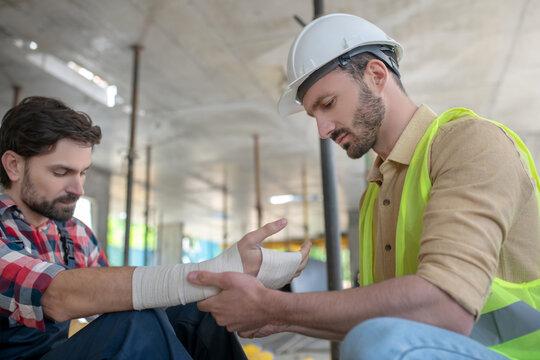Building worker in helmet applying bandage on his coworker forearm