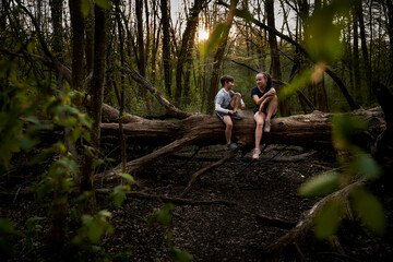Full length of smiling siblings talking while sitting on fallen tree in forest