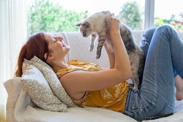 Young woman lying on the couch at home holding her cat