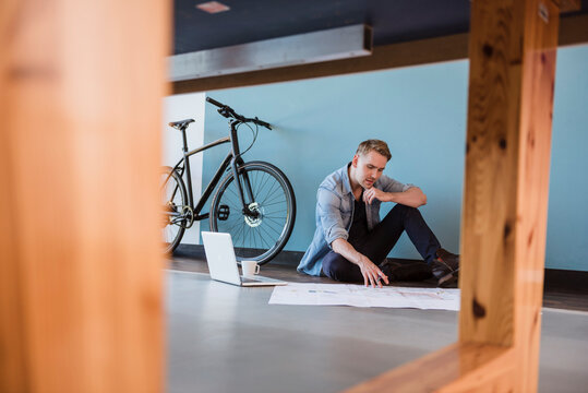Casual businessman sitting on floor of loft office, working on a blueprint