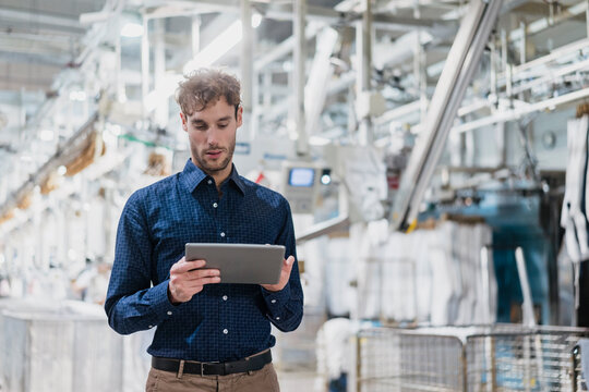 Young businessman using tablet in a factory