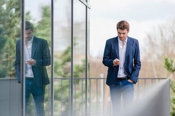 Young businessman using smartphone at an office building Wall mural