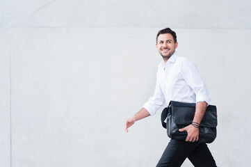 Smiling businessman with laptop bag walking along white wall