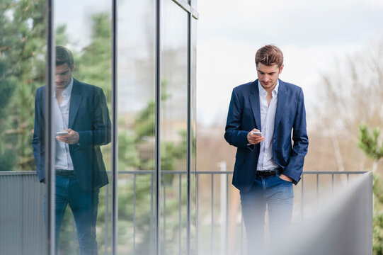 Young businessman using smartphone at an office building