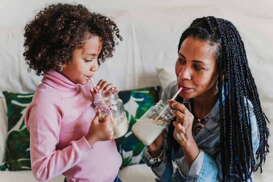 Mother and her little daughter drinking smoothies at home