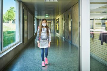 Girl wearing mask walking on school corridor