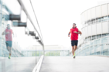 Young man jogging on footbridge in the city