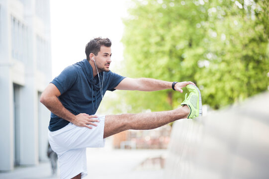Young man stretching his leg on wall in the city