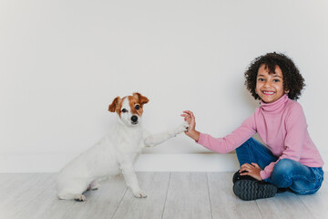 Portrait of smiling little girl sitting on the floor with her dog giving paw