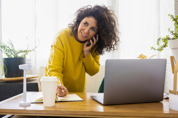 Woman on the phone working at desk in home office