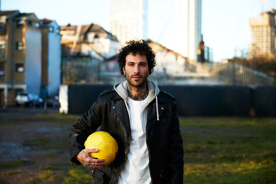 Man holding yellow football in the city