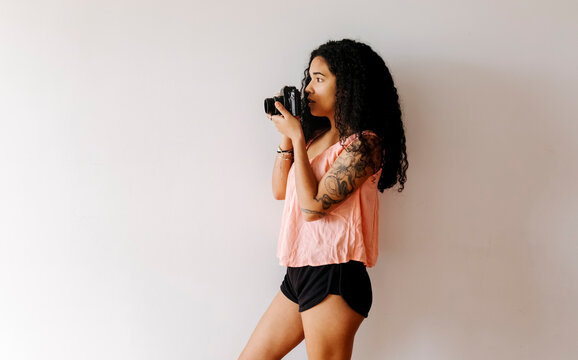 Young woman standing at a wall holding vintage camera