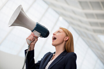 Businesswoman shouting into bullhorn