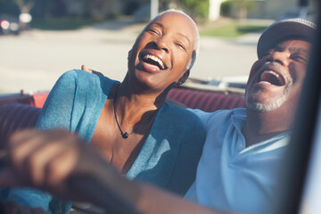 Older couple laughing in convertible