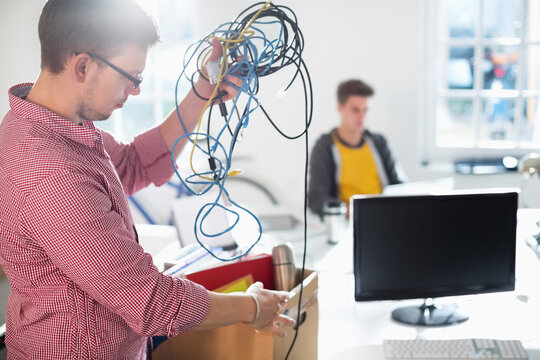 Businessman untangling cords in office