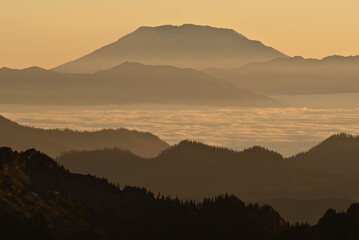 Silhouette of mountain over foggy landscape Wall mural