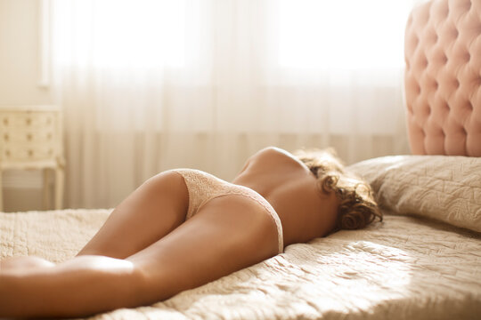 Nude woman wearing panties on bed