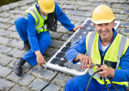 Workers installing solar panel on roof