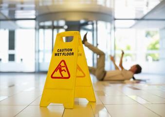 Obraz Businessman slipping on wet office floor - fototapety do salonu