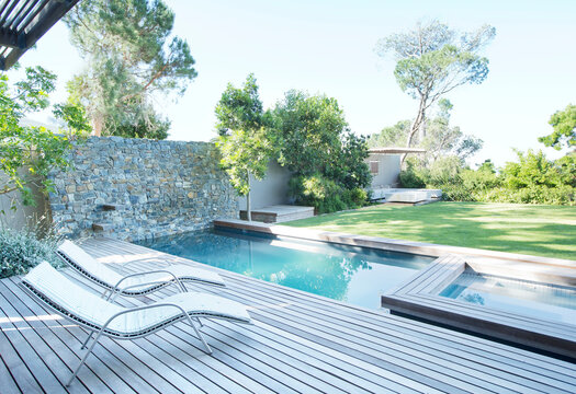 Lawn chairs and swimming pool in backyard
