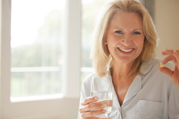 Portrait of smiling woman holding pill and glass of water