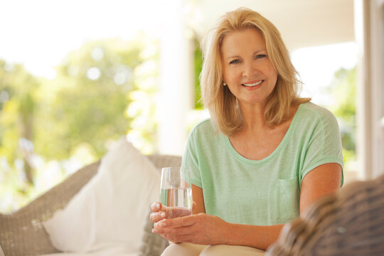 Portrait of smiling woman drinking water on patio
