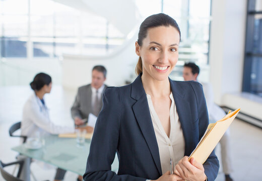 Portrait of smiling businesswoman in meeting with doctors