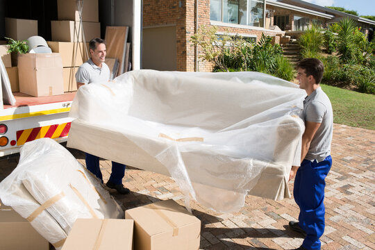 Movers carrying sofa from moving van in driveway