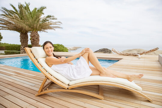 Woman relaxing in lounge chair at poolside