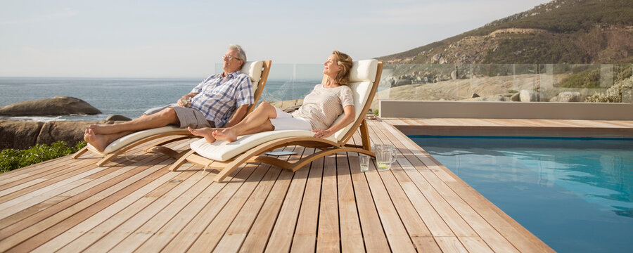 Older couple relaxing in lawn chairs by pool
