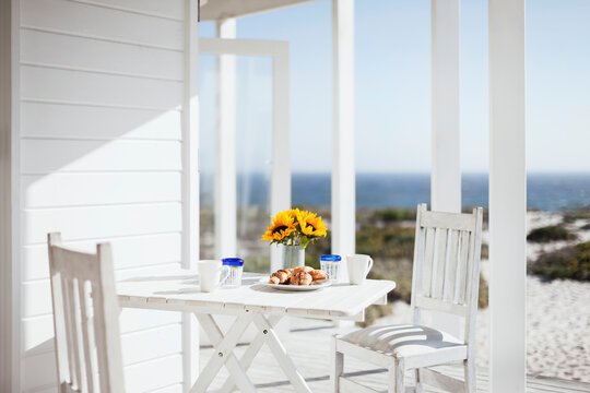 Vase of flowers, coffee and pastries on patio table overlooking ocean