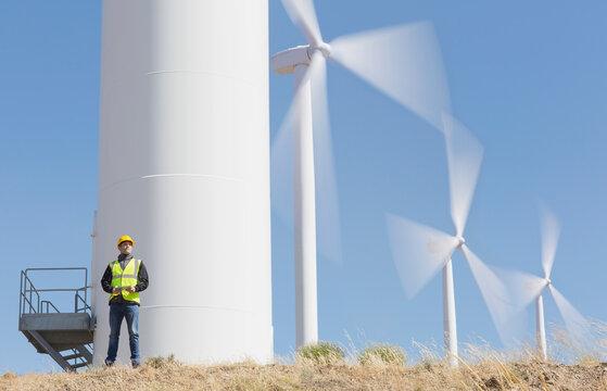Worker by wind turbines in rural landscape