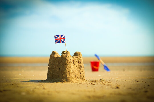 British flag in sandcastle on beach