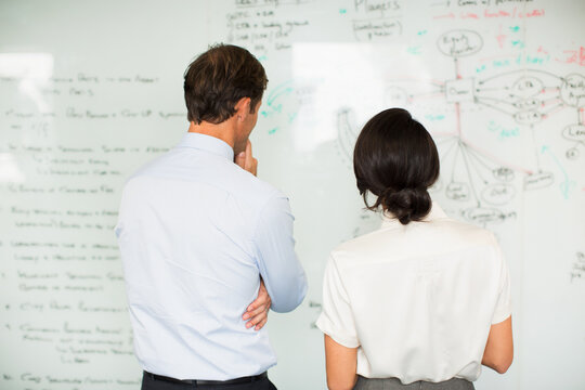 Business people reading whiteboard in office