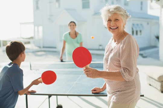 Multi-generation family playing table tennis outside beach house
