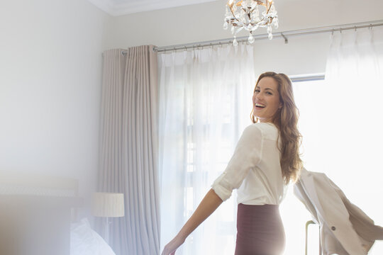 Businesswoman getting dressed in hotel room
