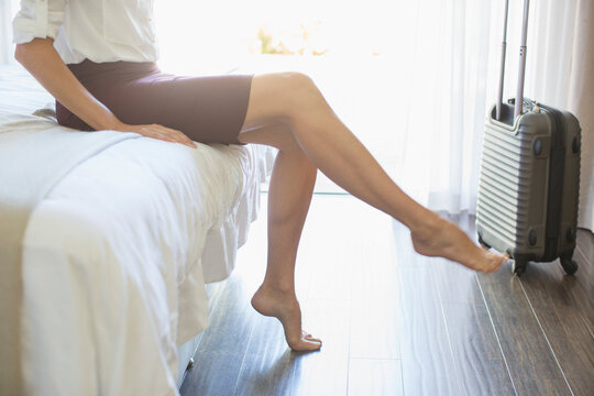 Businesswoman taking shoes off in hotel room