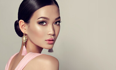 Asian model  fashion girl  with tassel earrings and  pink dress.  Oriental girl model, cosmetics, cosmetology and fashion.