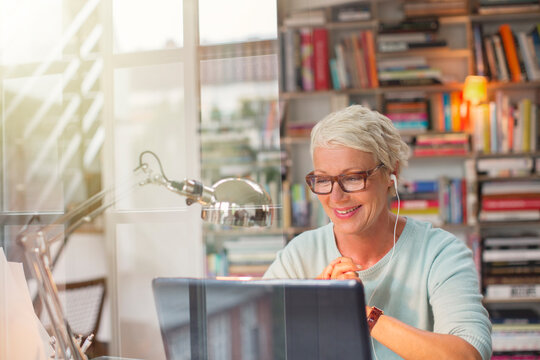 Businesswoman listening to earbuds and working in home office