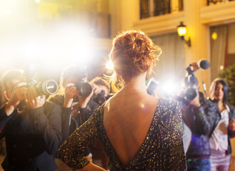 Celebrity being photographed by paparazzi photographers at event