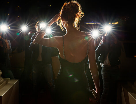 Silhouette of celebrity being photographed by paparazzi