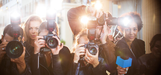 Portrait of paparazzi in a row with cameras and microphone