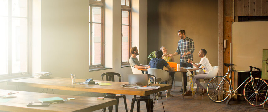 Creative businessman leading meeting at table in office