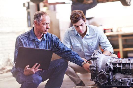Mechanic with laptop and customer examining engine in auto repair shop